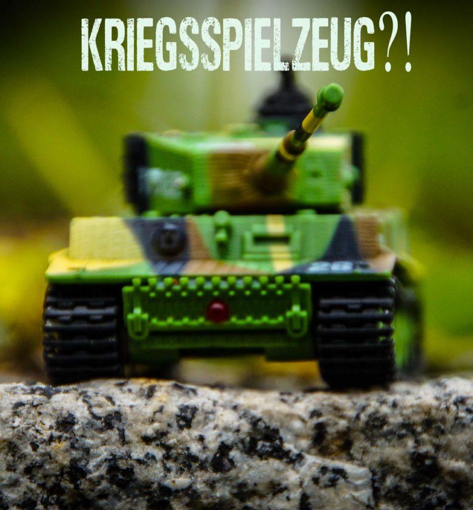 """Nahaufnahme Spielzeugpanzer Frontansicht auf einen Stein mit der Überschrift """"Kriegsspielzeug?!"""""""
