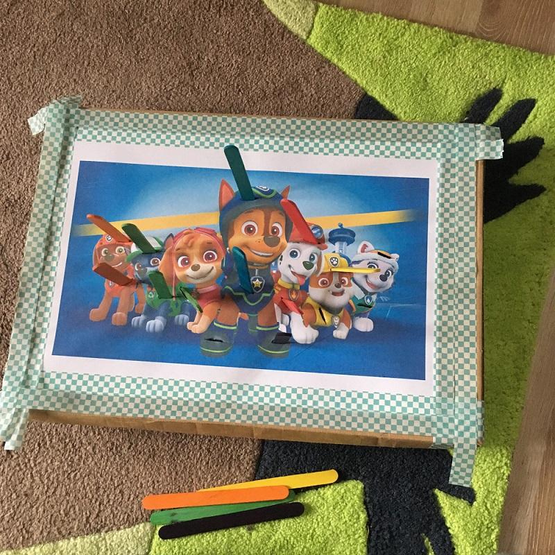 Selbstgemachtes Steckspiel aus einem Karton, einen ausgedruckten bunten Bild und bunten Eisstielen aus Holz.