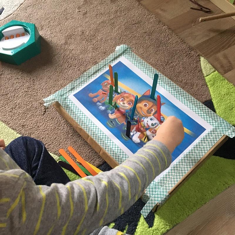 Kind spielt mit selbstgemachten Steckspiel. Bunte Eisstiele werden in die bunte Motiv zur passenden Farben rein gesteckt.