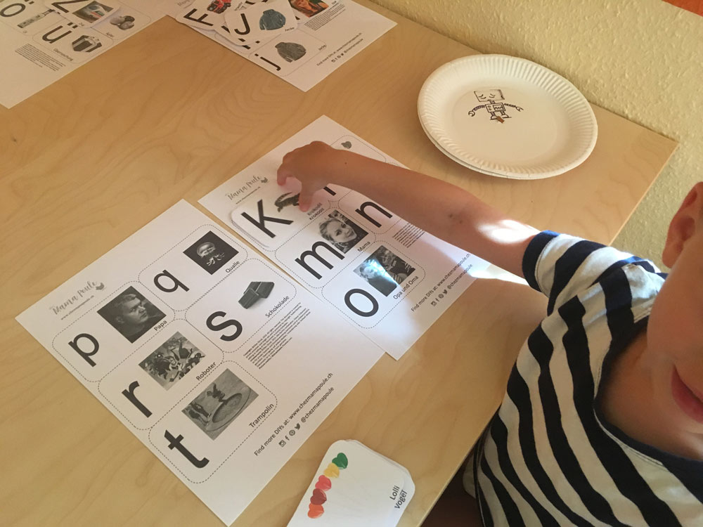 Kind spielt mit selbst gemachten Buchstaben Karten. Die Karten haben einmal Großbuchstaben und einmal Kleinbuchstaben. Die zueinander gehörenden Karten müssen vom Kind gefunden werden. Durch Motive, die dem Kind gefallen fällt das Lernen leichter. Dieses Spiel hilft beim Lernen der Groß- und Kleinbuchstaben und schließlich zum Lesen lernen.