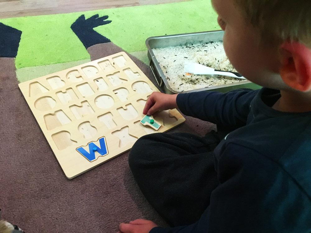 Kind spielt mit Buchstaben Puzzle. Die Buchstaben sind in einen flachen Gefäß unter Reis versteckt. Dieses Spiel ist einer der ersten Schritte zum Buchstaben und schließlich zum Lesen lernen.