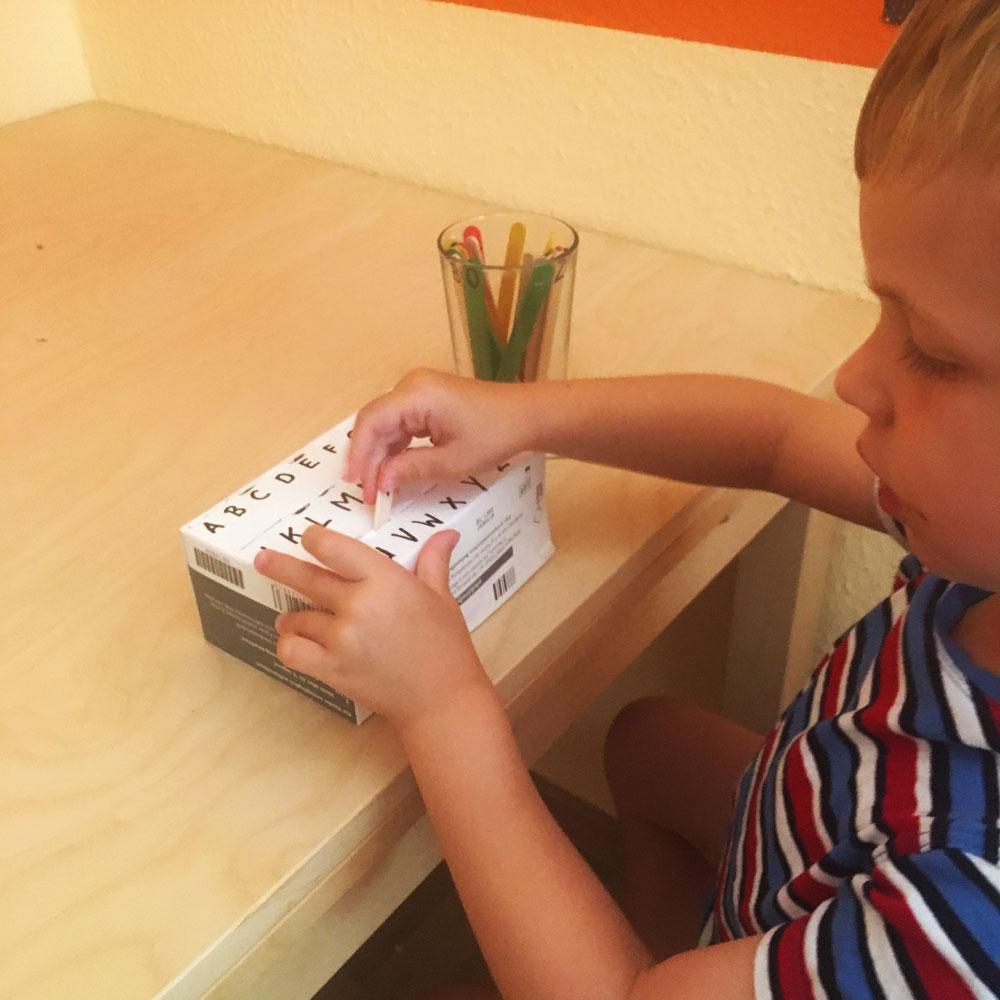 Kind spielt mit Buchstaben Steckspiel. Die Buchstaben sind auf Eissteilen geschrieben, die in den passend beschrifteten Schlitz in einer Pappschachtel gesteckt werden müssen. Dieses Spiel ist einer der ersten Schritte zum Buchstaben und schließlich zum Lesen lernen.