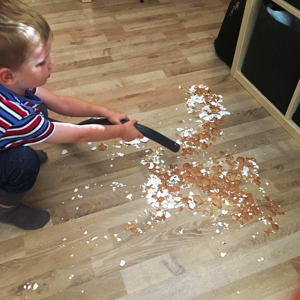 Kaputte Eierschalen werden danach vom Kind mit Staubsauger aufgeräumt
