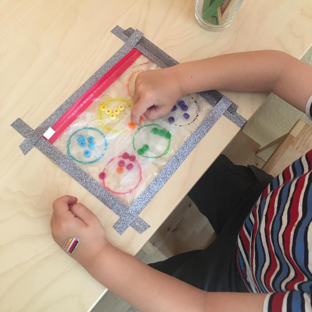Ideen zur Beschäftigung für Kinder: Kind sortiert bunte Perlen, die sich in einen Gefrierbeutel mit Haargel befinden.
