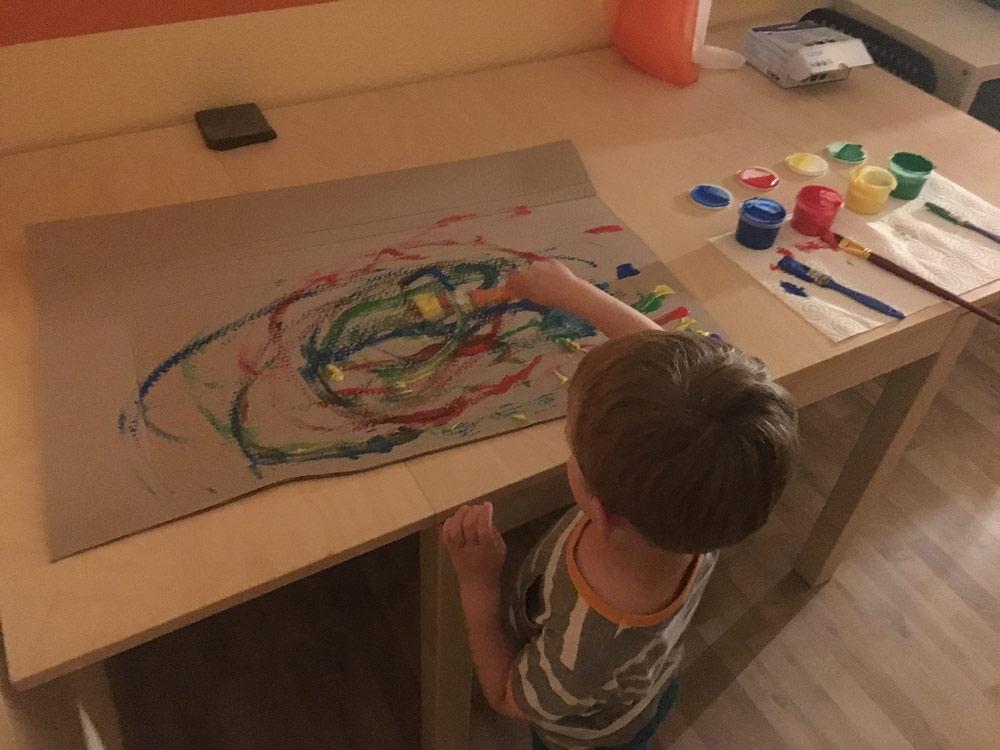 Ideen zur Beschäftigung für Kinder: Kind malt mit Fingerfarbe und Pinsel einen großen Karton bunt an.