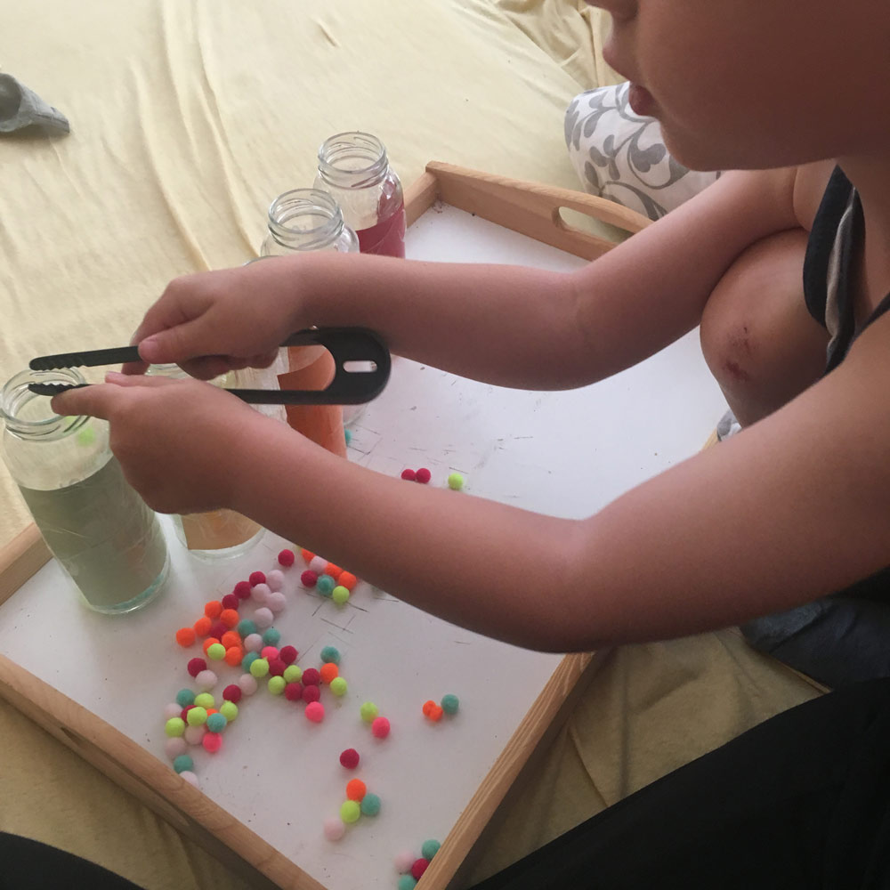 Kind sortiert bunte Pom Poms mit einer kleinen Küchenzange