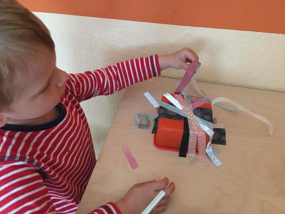 Ideen zur Beschäftigung für Kinder: Kind packt eine Dose aus, die mit Washi Tape zugeklebt war. In der Dose befindet sich eine Überraschung.